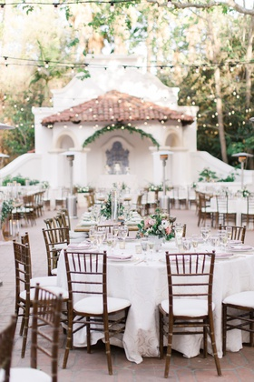 wedding reception courtyard bistro lights wood chair white linen green pink flower centerpieces