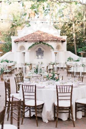 wedding reception courtyard bistro lights wood chair white linen green pink flower centerpieces