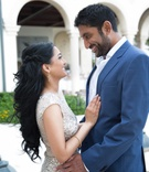Indian bride-to-be in a silver sequined dress with Indian groom-to-be in blue suit