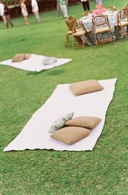 Beach towels on grass next to reception tables