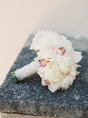 a bridal bouquet of white garden roses and peonies and pink orchids