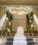 Ceremony structure with green vines and white flowers and drapery