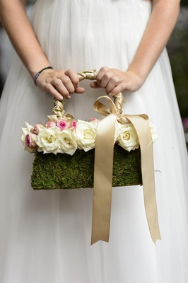 Flower girl carrying moss-covered hand bag