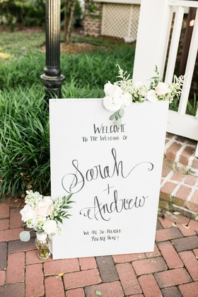 wedding welcome sign on brick floor outdoors white flowers greenery decorations hand written text