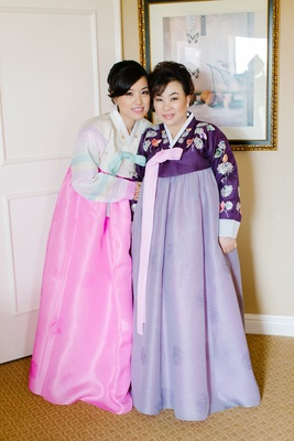 bride and mother wear traditional korean hanbok dresses.