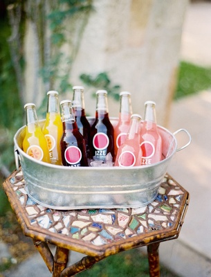 Yellow, red, and pink sparkling soda drinks in bucket