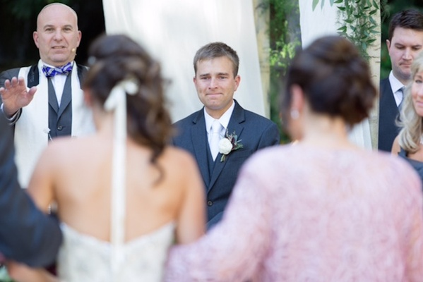 grooms holds back tears as the bride walks down the aisle