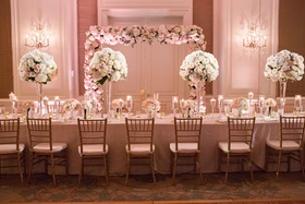 long reception table pink white tall small centerpieces flower structure greenery gold chairs
