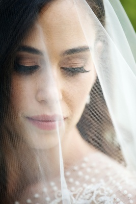 Close up of bride behind veil long eyelashes neutral makeup pink lip blush freckles Sabrina Dahan