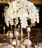 Orchid, hydrangea, ranunculus wedding flower arrangement on gold stand mercury glass candle holders