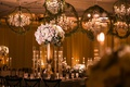 wedding reception tall centerpiece white pink flowers gold stand candleholders chandelier orb