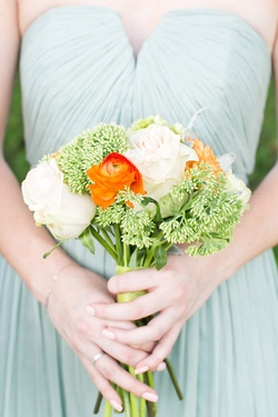Bridesmaid in a seafoam J.Crew dress holds bouquet of white roses, red orange ranunculus and greener