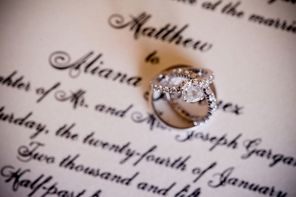 Engagement ring with diamond band and solitaire with wedding bands on classic invitation