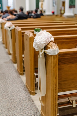 Wedding ceremony at church catholic couple flowers and ribbon on some church pews wood pew