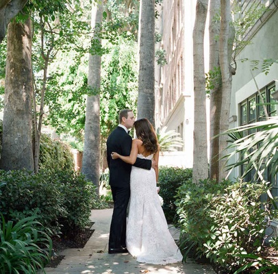 Groom in a black tuxedo & bride in a strapless Alencon lace gown in garden at Jonathan Club