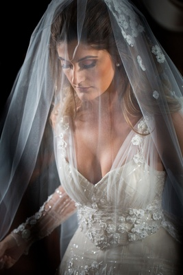 Wedding portrait bride in wedding dress v neck illusion tulle veil over face long hair down flowers