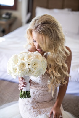 bride with long blonde hair curls galia lahav wedding dress bridal suite sniffs bouquet white roses