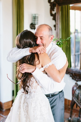 bride in off shoulder strap galia lahav wedding dress long hair hugging father in bridal suite dad