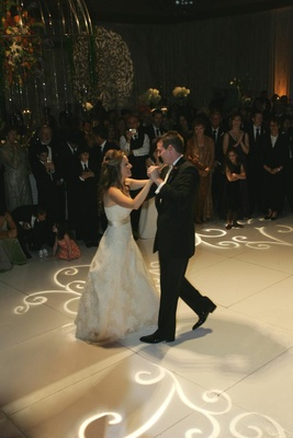 Bride and groom dancing on white dance floor