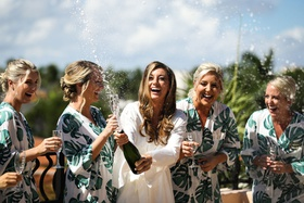 bride popping champagne with bridesmaids in tropical print robes monstera leaf design outside