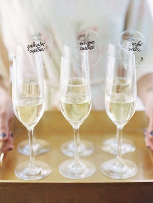 Champagne flutes filled with bubbly and Lucite acrylic circles with calligraphy and table numbers