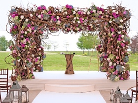 An array of stunning blooms and branches create a striking wedding canopy.