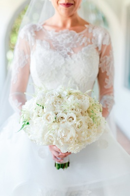 ivory bridal bouquet with roses and peonies held by bride in lace ball gown