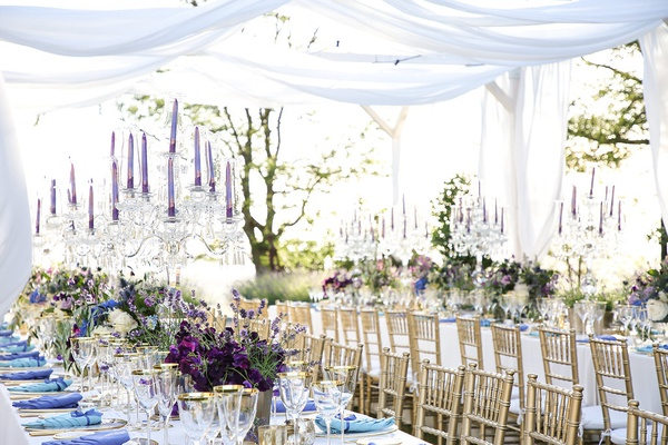 outdoor wedding reception setting with purple tapered candles and crystal candelabra