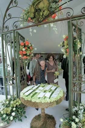Wedding reception place card table is covered in moss and topped with green carnations