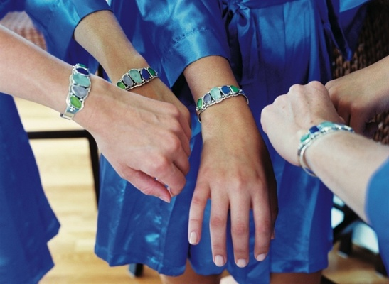 Bridesmaids in blue dresses with colorful bracelet cuffs