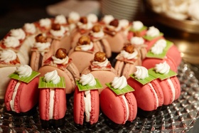 Pink and tan macaron desserts with toppings on crystal tray