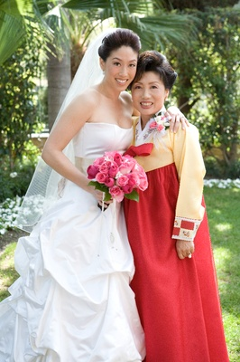 bride wearing western style gown and mom wearing traditional korean gown