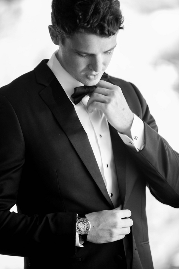 groom in black tuxedo and bow tie finishes getting ready for the wedding