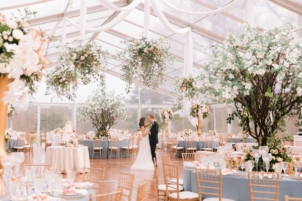 bride and groom photo in clear tent reception photo decor dogwood trees flower chandeliers drapery