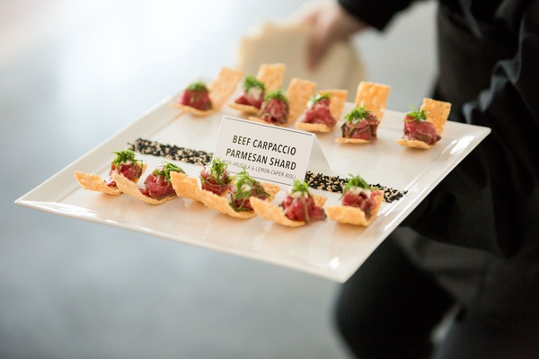 beef carpaccio on a parmesan shard with arugula and lemon caper aioli hors d'oeuvre appetizer event