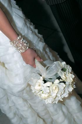 bride wearing bracelet holds white flower bouquet