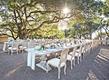 Wedding reception long tables rustic chairs low centerpiece succulents flowers fruit lanterns sun