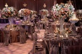 Wedding reception opulent crystal centerpiece base with pink, orange, rose flowers and grey chairs