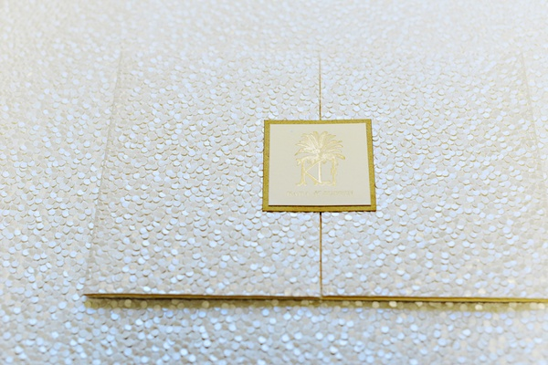 Sequined wedding invitation with a gold seal of the wedding crest