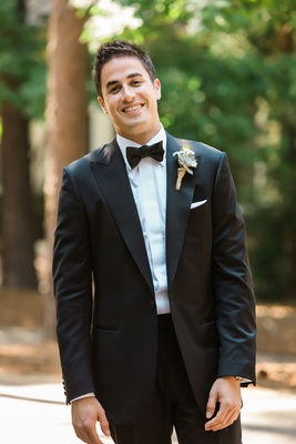 Groom in tuxedo with bow tie and rustic succulent wedding boutonniere