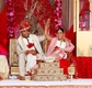 Indian bride in red lehenga and Indian groom in white sherwani at wedding ceremony