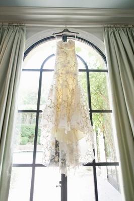 Claire Pettibone wedding dress hanging in window