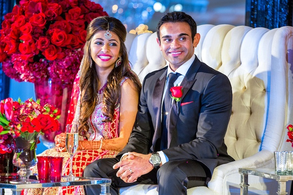 Indian newlyweds on tufted white loveseat at reception