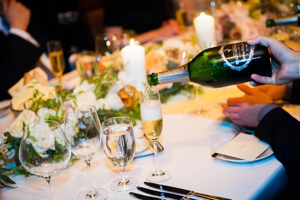 Server pours Champagne into wine flute for guest at a wedding reception table with light flowers