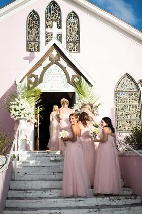 Bridesmaids in light pink blush bridesmaid dresses walking up stairs into light pink church Bahamas