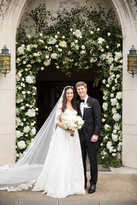 bride in lace trim wedding veil with groom in suit bow tie in front of church arch greenery white