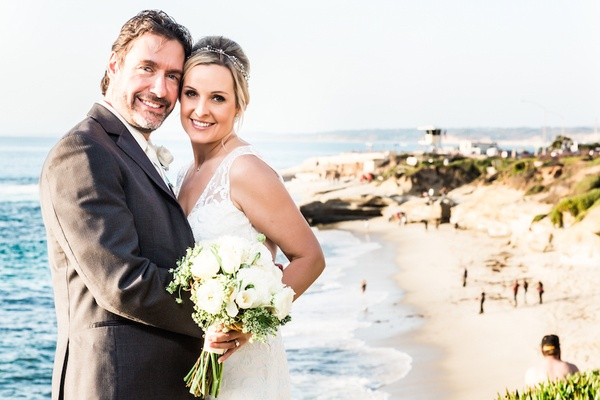 Bride in a sleeveless Claire Pettibone dress, groom in grey suit at La Jolla beach
