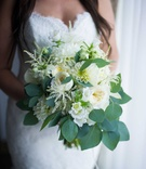 a bridal bouquet made up of varying white flowers and leafy green foliage