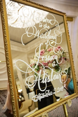 wedding reception welcome sign gold frame mirror white calligraphy script and wedding date