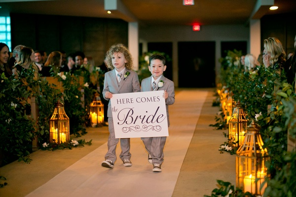 Wedding ceremony at church lanterns and greenery along aisle white aisle runner grey ring bearer